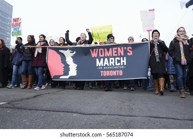 """TORONTO - JANUARY 21: People with anti-Trump messages and signs walking during the """"Women's March on Washington"""" to protest against Trump presidency on January 21, 2017 in Toronto, Canada."""