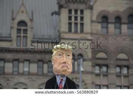 "TORONTO - JANUARY 21: A protestor carrying a paper idol of President Donal Trump during the ""Women's March on Washington"" to protest against Trump presidency on January 21, 2017 in Toronto, Canada."