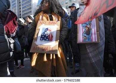 """TORONTO - January 30: Protesters holding """"we the people"""" signs during a protest in front of the US Consulate to denounce Donald Trump's immigration policies on January  30, 2017 in Toronto, Canada."""