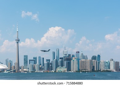 TORONTO - July 17, 2015: Toronto cityscape with a plane flying over the city. Lake Ontario, Canada