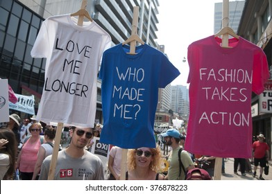 TORONTO - JULY 5 :  A couple with  t-shirts asking for cleaner and sustainable fashion industry during the Jobs,Justice and Climate rally on July  5, 2015 in Toronto, Canada.