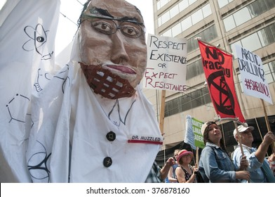 """TORONTO - JULY 5 :  Masked protesters with signs asking to stop """"arctic drilling """"during the Jobs,Justice and Climate rally on July  5, 2015 in Toronto, Canada."""