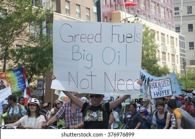 TORONTO - JULY 5 :  People with signs denouncing greed of oil companies during the Jobs,Justice and Climate rally on July  5, 2015 in Toronto, Canada.