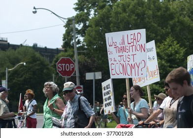 TORONTO - JULY 5 : People walking on the street with banners  asking the leaders to not think of economy alone  during the Jobs,Justice and Climate rally on July  5, 2015 in Toronto, Canada.