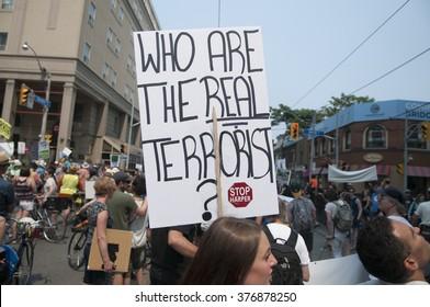 TORONTO - JULY 5 :  A woman holding a sign comparing politicians  with climate terrorists during the Jobs,Justice and Climate rally on July  5, 2015 in Toronto, Canada.