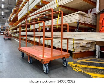 Toronto - June 25, 2019: A shopping cart holds several pieces of wood in the lumber section of a big box home improvement store.
