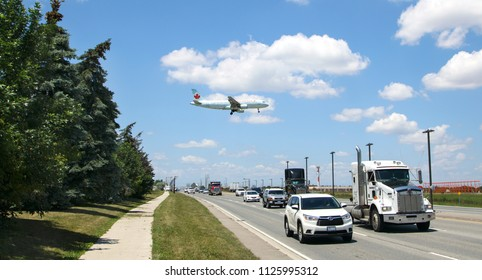 TORONTO - JUNE28, 2018. Air Canada Boeing 737 is landing at Toronto Pearson Airport on June 28, 2018. Airplane flying over the busy road.