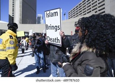 "TORONTO - March 4: An Anti Muslim supporter with a sign saying ""Islam brings death"" being cordoned off by the police during a pro and anti Muslim gathering on March 4, 2017 in Toronto, Canada."