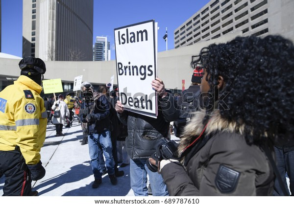 """TORONTO - March 4: An Anti Muslim supporter with a sign saying """"Islam brings death"""" being cordoned off by the police during a pro and anti Muslim gathering on March 4, 2017 in Toronto, Canada."""