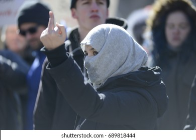 """TORONTO - March 4:   A  supporter showing her """"middle finger"""" to the anti Muslim supporters during a pro and anti Muslim gathering on March 4, 2017 in Toronto, Canada."""