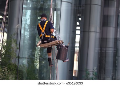 TORONTO, MAY 1, 2012: Working washing the outside windows of a modern office building