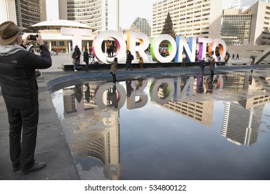 TORONTO - NOVEMBER 18,  2016: People taking pictures in front of the famous Toronto sign at Nathan Phillips Square with reflection in the fountain.