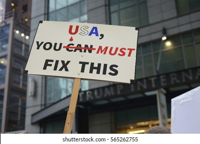 "TORONTO - NOVEMBER 19: A protester waiving a sign stating to ""fix the issue"" with Donald Trump's presidency during a protest in front of Trump Tower on November  19, 2016 in Toronto, Canada."