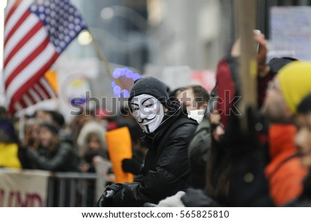 "TORONTO - NOVEMBER 19: A protester wearing a ""guy fawkes"" mask standing among the crowd during a protest in front of Trump Tower on November  19, 2016 in Toronto, Canada."