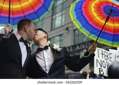 TORONTO - NOVEMBER 19: Trans couple Matthew and Miguel kissing each other during a protest in front of Trump Tower on November  19, 2016 in Toronto, Canada.