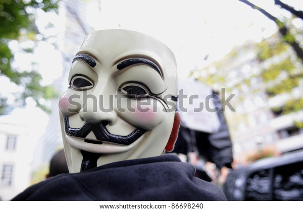 TORONTO - OCTOBER 15: A protestor listens to the speeches with his mask  tied to his shoulder during the Occupy Toronto Movement on October 15, 2011 in Toronto, Canada.