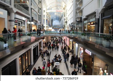 TORONTO - October 16, 2017: Shoppers Visit The Toronto Eaton Center, Interior Architecture Of Shopping Mall In Downtown Toronto, Crowded Fashion, Technology And Other Stores, Busy Metropolitan Area