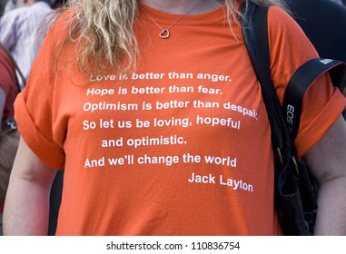 TORONTO, ON CANADA - 22 AUG:  Woman presenting T-shirt with a quote at the Jack Layton chalk memorial at Nathan Phillips Square on August 22, 2012 in Toronto, ON, Canada.