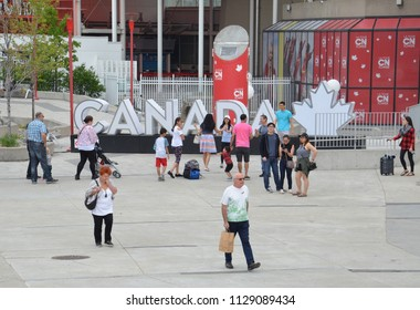 TORONTO, ON / CANADA - MAY 26, 2018: Tourists take photos of each other at the CANADA sign near the CN tower in downtown Toronto, originally erected on the 150th anniversary of Canada.