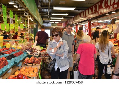TORONTO, ON / CANADA - MAY 26, 2018: Shoppers walk past the fruit market inside the St. Lawrence Market.