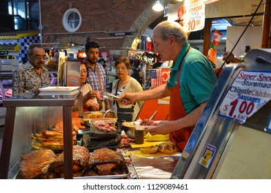 TORONTO, ON / CANADA - MAY 26, 2018: A storekeeper hands out samples inside the St. Lawrence Market.