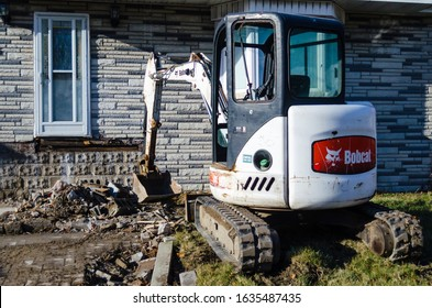 Toronto, ON/Canada - 1/20/2020: Compact Bobcat excavator working at the front of a house.