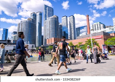 Toronto, Ontario, Canada - 2019 06 30: Torontonians and tourists walking along the promenade in the Harbourfront Toronto in front of high rise buildings in downtown Toronto