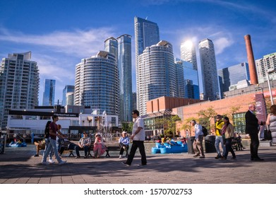 Toronto, Ontario, Canada - 2019 06 09: Torontonians and tourists walking along the promenade in the Harbourfront Toronto in front of high rise buildings in downtownToronto