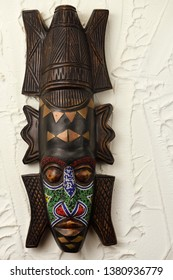 Toronto, Ontario, Canada - April 23, 2019: Ashanti carved wood ceremonial mask from Ghana with beads and brass on stucco wall