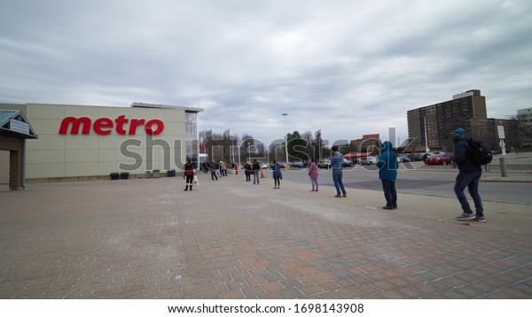 Toronto, Ontario, Canada - April 7, 2020 : Metro Store. Social distancing practice. People in line one meter distance from each other outside store during Covid-19 coronavirus world wide pandemic.