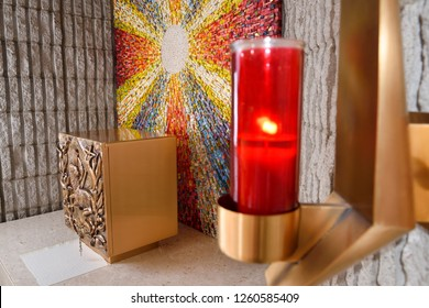 Toronto, Ontario, Canada - August 20, 2917: Red Sanctuary Lamp or Eternal Flame at the Tabernacle with bronze Lamb of God bas relief at side altar with sunburst mosaic in Catholic church