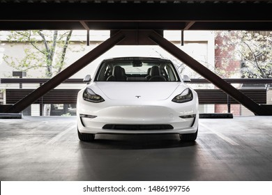 Toronto, Ontario / Canada - August 23rd 2019 : Photograph of a white Tesla model 3 parked in an indoor parking.