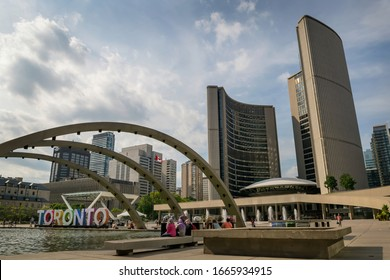 Toronto, Ontario / Canada - August 30, 2016: Toronto City Hall and Nathan Phillips Square with arches stretching across the pond and the Toronto sign all under a blue sky with clouds