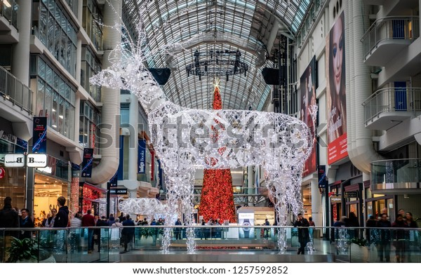 Toronto, Ontario, Canada - Dec 12, 2018: Busy Christmas shoppers walk by a huge white reindeer, illuminated with white lights, inside the Eaton Centre mall.