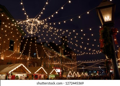 Toronto, Ontario, Canada - December 17, 2015: Lights strung over Trinity Street Distillery District for the Toronto Christmas Market with gas lamp