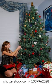 Toronto, Ontario, Canada - December 23, 2006: Young girl preparing christmas presents and decorations on the tree