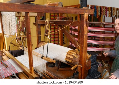 Toronto, Ontario, Canada - December 30, 2008: Weaver in 1850 shop with colorful yarn and hand loom at Pioneer Village Toronto