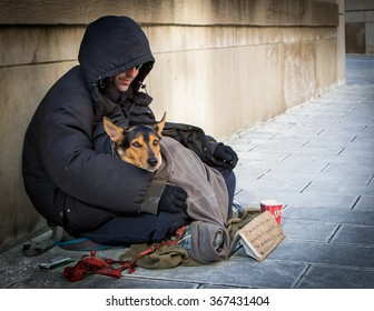 TORONTO, ONTARIO, CANADA - January 23, 2016: A homeless man and his homeless dog beg for small change outside Union Station, Toronto's main train station.