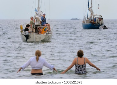 Toronto, Ontario, Canada - July 18, 2010: Two women wading out to friends in a sailboat through cold Lake Ontario water