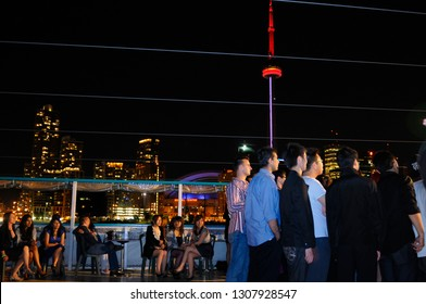 Toronto, Ontario, Canada - July 2, 2010: Boys watching limbo dancing while girls sit and rest on a boat cruise with Toronto skyline at night