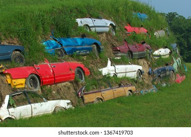 Toronto, Ontario, Canada - July 21, 2004: Salvaged Cars Buried in the side of a Hill