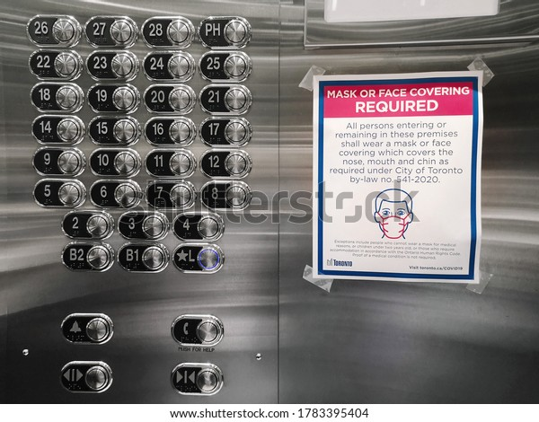 Toronto, Ontario, Canada - July 24, 2020: Warning notice on elevator lift wall to wear protection face mask when entering. Precaution against coronavirus covid-19 spread. New normal rules.