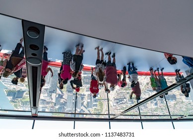 Toronto, Ontario, Canada - July 3, 2018:  Upside-down reflection of CN Tower visitors in glass ceiling on west side of LookOut Level.