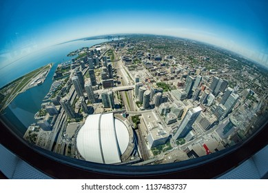 Toronto, Ontario, Canada - July 3, 2018:  Fisheye view looking west from top of CN Tower along Lake Ontario toward Etobicoke district in summer; Rogers Centre at bottom left.