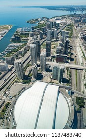 Toronto, Ontario, Canada - July 3, 2018:  Looking west from top of CN Tower along Lake Ontario, vertical orientation.  Rogers Centre at bottom, Gardiner Expressway lower left to upper right.