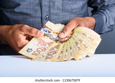 Toronto, Ontario / Canada - July 9, 2018: A businessman hands counting Canadian hundred dollar bills, entrepreneur counting money.