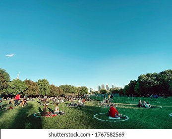 Toronto, Ontario, Canada - June 12, 2020: People sitting in painted circles in Trinity Bellwoods park keeping social distancing. Isolation and distance during covid-19 coronavirus pandemic in Toronto.