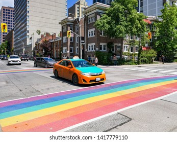 Toronto, Ontario, Canada - June 6, 2019: Toronto city getting ready to Pride Parade on Church street. Festive rainbow coloured flag on crosswalk for pedestrians.