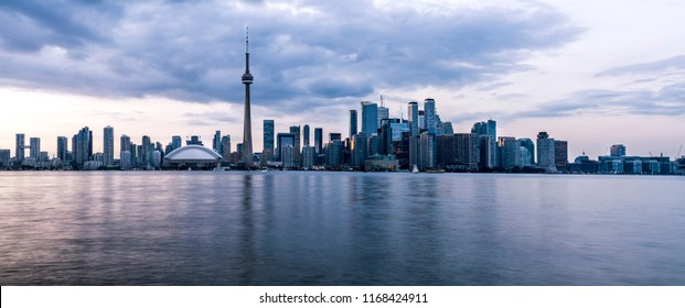 Toronto, Ontario - Canada. Long exposure of wide panorama of Toronto, Ontario - Canada. Bright sky with a smooth water surface. Beautiful city lights seen from the Toronto Island.