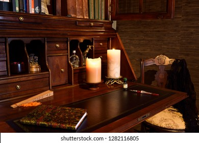 Toronto, Ontario, Canada - March 18, 2015: Antique secretary writing desk in dark room with candles